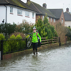 © London News Pictures. 12/02/2014. Egham, UK.  A resident carrying his bike over flood water in Egham, Surrey, which has been hit by heavy flooding. Torrential  rain in the area is due to raise water levels increasing the risk of further flooding. Photo credit : Ben Cawthra/LNP