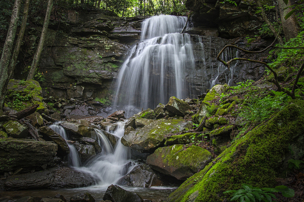 The approach to Kate's Falls, found in the Glade Creek area of the New River Gorge in West Virginia, takes on a mystical quality as the falls drape over a cliff side taking the form of a skeletal hand reaching down into a vibrant, green landscape under the forest canopy.