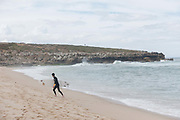 A male surfer walking from the water at Foz do Lizandro on 26th May 2018 in Ericeira in Portugal. Ericeira is a civil parish and seaside resort/fishing community on the western coast of Portugal.