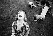 """A four year-old girl throws a tantrum while playing with her young two-year-old brother in the back garden of their South London home. We look down on the small girl who throws her head back in a rage, mouth wide open, after not getting what she wants. But in the background, her younger sibling is oblivious to her emotional outburst and gets on with playing at the foot of a children's garden slide - in an innocent world of his own. From a personal documentary project entitled """"Next of Kin"""" about the photographer's two children's early years spent in parallel universes. Model released."""