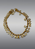 Bronze Age Hattian gold necklace from Grave TM, possibly a Bronze Age Royal grave (2500 BC to 2250 BC) - Alacahoyuk - Museum of Anatolian Civilisations, Ankara, Turkey. Against a gray background .<br /> <br /> If you prefer to buy from our ALAMY PHOTO LIBRARY  Collection visit : https://www.alamy.com/portfolio/paul-williams-funkystock/royal-tombs-alaca-hoyuk-bronze-age.html (TIP refine search by adding background colour in the LOWER search box)<br /> <br /> Visit our ANCIENT WORLD PHOTO COLLECTIONS for more photos to download or buy as wall art prints https://funkystock.photoshelter.com/gallery-collection/Ancient-World-Art-Antiquities-Historic-Sites-Pictures-Images-of/C00006u26yqSkDOM