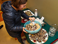"""Alison Howe fills her container with homemade cookies during the """"Cookie Swap"""" held at the Gilford Library Tuesday evening.    (Karen Bobotas/for the Laconia Daily Sun)"""