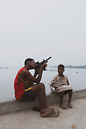 Early on a foggy morning, a teenager playing with a toy gun sits with a boy on a dock at the Sepik River in the small town of Angoram, Papua New Guinea.<br /><br />(July 23, 2017)