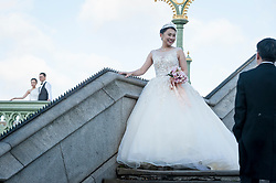 © Licensed to London News Pictures. 05/11/2017. London, UK.  A pair of mainland Chinese couples pose for pre-wedding photographs being taken on Westminster Bridge.  With Sterling's decline, London is seen as an ever more affordable location for such photographs, as well as providing memorable landmarks as backdrops.  Frequently, the photographer and team are also flown out from China to capture the images.  Photo credit: Stephen Chung/LNP
