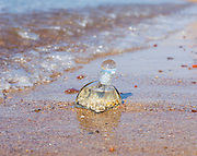 A bottle with seashells embedded in the sand on the beach