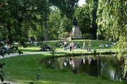 Het Vondelpark in Amsterdam. Opgericht in 1864 is het 140 jaar oude park, dat sinds 1996 Rijksmonument is, is boeiend, veelzijdig en uiterst in trek bij jong, gemiddeld  en oud. Wandelen, de hond uitlaten, skaten, joggen, picknickken, zwemmen met de kinderen, voetballen. Jaarlijks krijgt het Vondelpark gemiddeld 10 miljoen mensen op bezoek, per vierkante meter is dat meer dan het Central Park in New York! Het Vondelpark is ontworpen in de Engelse landschapstijl. Met behulp van kenmerken uit deze stijl is een park gecomponeerd dat de 19e-eeuwse Amsterdammer de illusie gaf van het perfecte natuurlijke landschap.<br /> <br /> The Vondelpark in Amsterdam. Set up in 1864, the 140 years old park has been since 1996 a monument and is captivating, multi-purpose and extremely in appetite at young, on average and old. To walk, skate, jog, picknick swimming with the children or play soccer. The Vondelpark has a average of 10 millions people a yeary, by square meter it is more that than the Central park more in New York! The Vondelpark have been devised in the English Style . Using characteristics from this style a park has been composed that 19th century and has to give the amsterdammer the illusion gave of the perfect natural landscape.<br /> In the centre the statue of Joost van den Vondel .