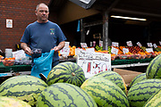 A market trader at an outdoor fresh fruit and vegetable stall bags a punnet of plums with rows of seedless watermelons in the foreground on 4th September, 2021 in Leeds, United Kingdom. A combination of Brexit and Covid-19 is reportedly exacerbating an already severe staff shortage in the British food industry, with a lack of fruit and vegetable pickers that could see a hike in food prices across the country.
