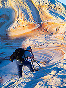 A photograper prepares to photograph the rock detail at White Pocket, Paria Plateau, Vermilion Cliffs National Monument, Arizona.