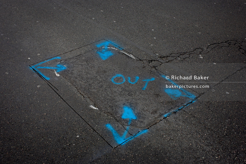 The word OUT has been sprayed on the broken road surface in Whitehall in Westminster, central London