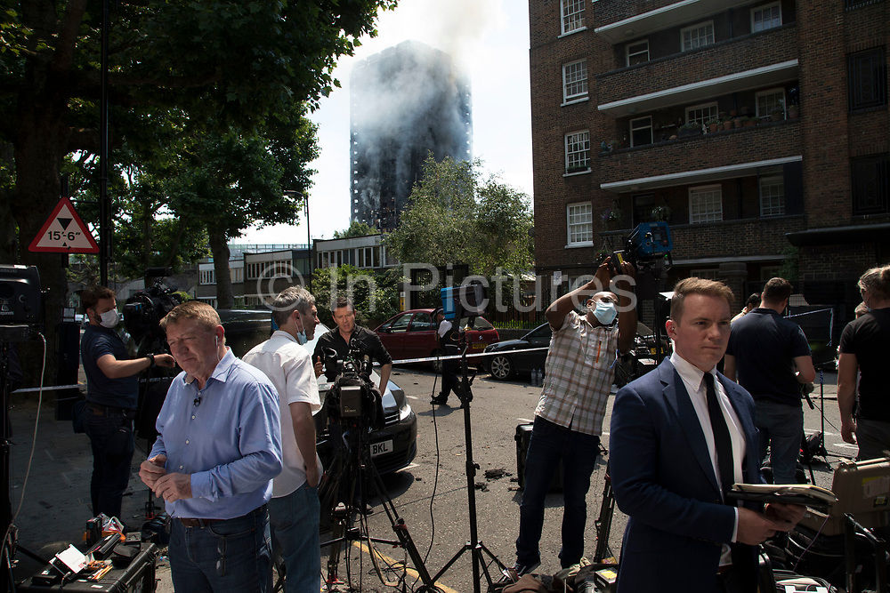 TV and other media reporting from near to a blaze at Grenfell Tower near Notting Hill on 14th June 2017 in West London, United Kingdom. The huge fire engulfed the tower block, trapping many people in their homes. A number of fatalities are reported. The block of flats in the Borough of Kensington and Chelsea,billowed large plumes of smoke way above the capital after the blaze broke out in the early hours of Wednesday morning. Londoners came out on the streets to help, offer food and water, support and assistance to those who had lost their homes or didn't know the whereabouts of their friends and family.