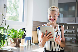 Young woman using digital tablet in the kitchen, Bavaria, Germany