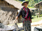 Wearing her traditional clothing, Meuay, a Iu Mien (Yao) ethnic minority woman boils indigo dyed cotton fabric in Mak Bao (a trailing forest fruit) to fix the colour, Ban Hom Phan, Houaphan province, Lao PDR. Meuay buys the cotton fabric from a nearby Tai Deng village and after dyeing the fabric many times to build up the colour she sells to local Iu Mien women to make their traditional clothing. One of the most ethnically diverse countries in Southeast Asia, Laos has 49 officially recognised ethnic groups although there are many more self-identified and sub groups. These groups are distinguished by their own customs, beliefs and rituals.