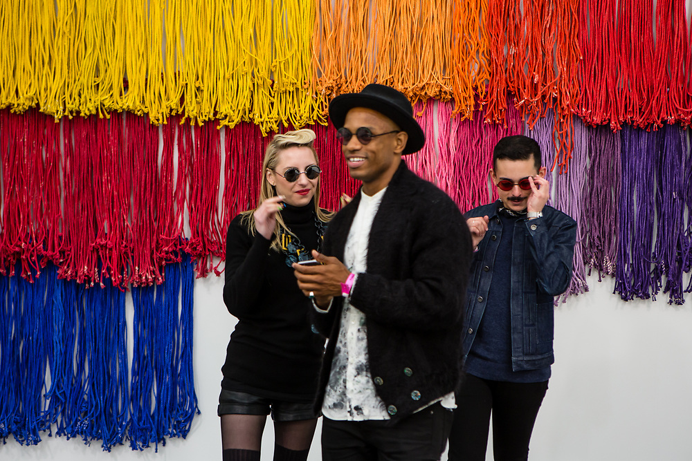 """New York, NY - 5 May 2017. The opening day of the Frieze Art Fair, showcasing modern and contemporary art presented by galleries from around the world, on Randall's Island in New York City. Visitors took photos in front of the late Emirati artist Hassan Sharif's """"Colors,"""" in the gallery of Isabelle van den Eynde from Dubai."""