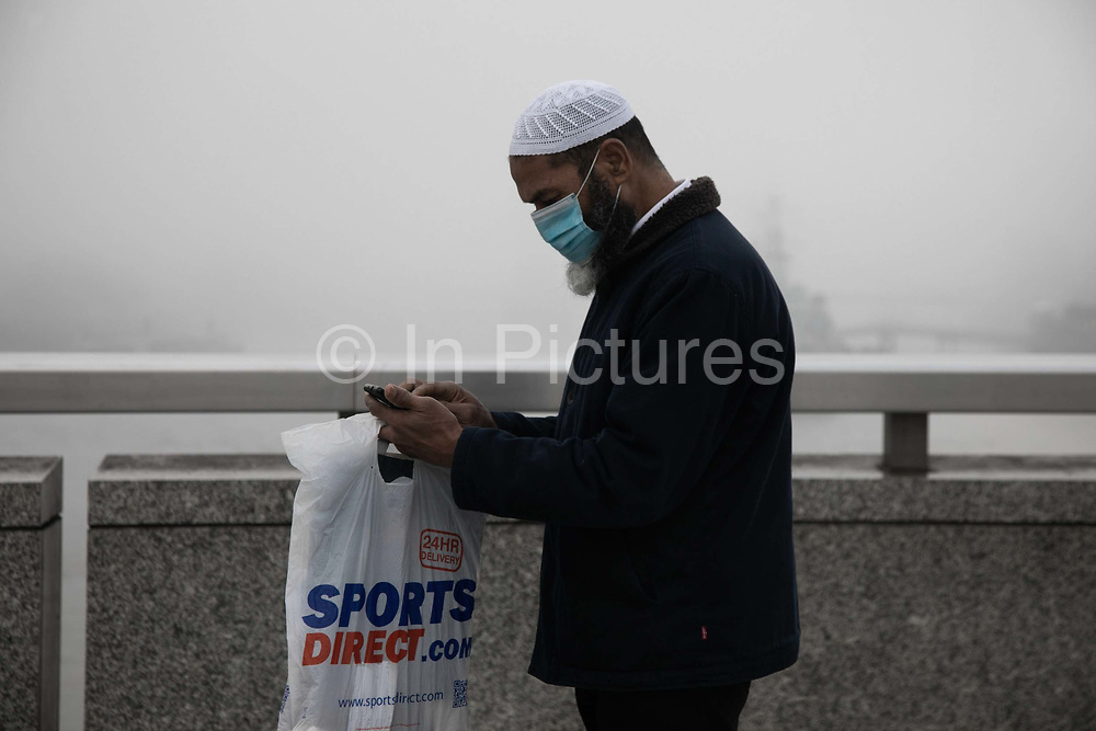 A muslim man wearing a face mask looks at his phone on the first day of national lockdown 5th of Novemeber 2020, London Bridge, London, United Kingdom. London Bridge is usually a busy with commuters walking across from London Bridge Station to the City of London but on the first day of lockdown the bridge is very quiet. The UK Govenrment introduced a 4 week lockdown from November 5th - December 2nd to combat the cororanavirus outbreak. It is the second national lockdown in the UK.