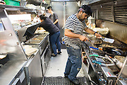 Hula Truck cook Angel Santos prepares dishes during Off the Grid at the Great Mall of the Bay Area in Milpitas, California, on May 12, 2016. (Stan Olszewski/SOSKIphoto)