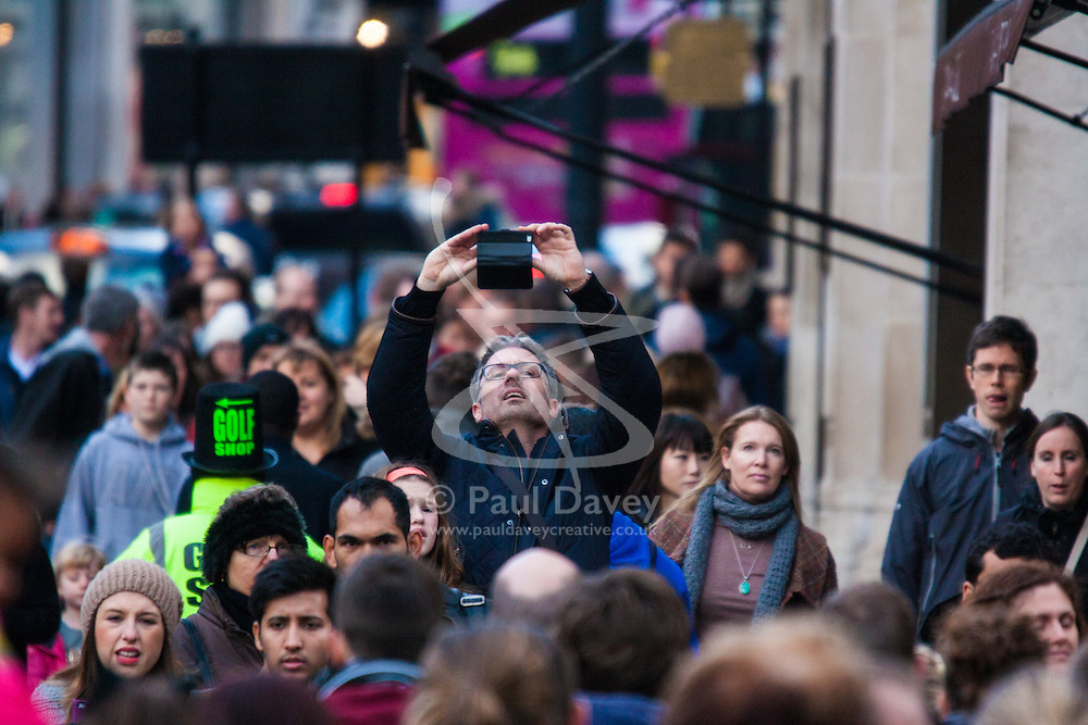 """London, December 20th 2014. Tens of thousands of shoppers descend on central London to scoop up pre-Christmas bargains as retailers offer discount incentives on """"Panic Saturday"""". PICTURED: A shopper takes an overhead picture of the huge crowds on Regents Street with his smartphone."""