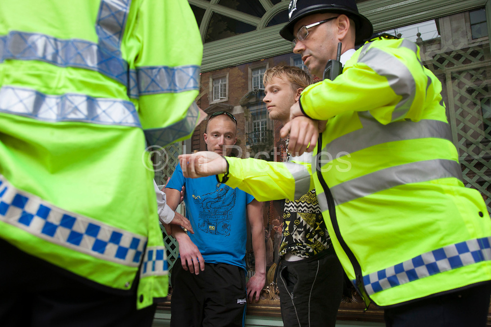 London, UK. Tuesday 11th June 2013. Protesters undergo stop and search tactics by police during demonstration against the upcoming G8 summit in central London, UK.
