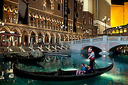 An oriental couple is enjoying a ride on an Italian gondola inside an artificial lake built in front of The Venetian Hotel, on The Strip, Las Vegas, Nevada, USA.