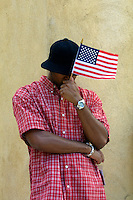 13 September 2001: NYC resident holds a flag and lowers hid head in disbelief of the Terrorist attack on the America's.  Lower Manhattan, NY. Area surrounding ground zero where the World Trade Centers WTC once stood only hours after they fell to the ground in New York.  Islamic terrorist Osama bin Laden declares The Jihad or Holy War against The United States of America on September 11, 2001. Headline news photos available for editorial use.