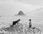 9902-D1. Children build a sandcastle on Cannon Beach ca. 1937.  Haystack rock in background