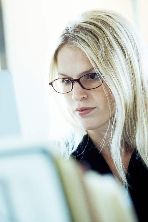 A portrait of a young woman working at a computer.