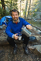 Camper pours fresh brewed coffee at Sykes Hot Springs, Big Sur, California.