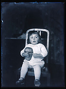 portrait of a toddler holding a basket toy France ca 1920s