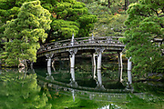 A bridge reflects in a pond at Kyoto Imperial Palace (Kyoto Gosho), in Kyoto, Japan. Kyoto Imperial Palace (Kyoto Gosho) was the residence of Japan's Imperial Family until 1868, when the emperor and capital were moved from Kyoto to Tokyo. Kyoto Gosho is within spacious Kyoto Imperial Park (Kyoto Gyoen National Garden) which also encompasses Sento Imperial Palace. The current Imperial Palace was reconstructed in 1855 after it had burnt down and moved around town repeatedly over the centuries. The complex is enclosed by long walls and has several gates, halls and gardens. The enthronement ceremonies of Emperors Taisho and Showa were held in the palace's main hall. Tokyo Imperial Palace is now used for enthronement ceremonies. The palace grounds (but not the buildings) can now be entered and explored without joining a tour and without any prior arrangements.