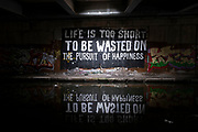 Life is too short to be wasted on the pursuit of happiness, a piece of poetic street art graffiti in the canal underpass at Gravelly Hill Interchange, aka Spaghetti Junction under Coronavirus lockdown, while far fewer vehicles pass overhead on 1st May 2020 in Birmingham, England, United Kingdom. The term Spaghetti Junction was originally used to refer to Gravelly Hill Interchange on the M6 motorway in an article published in the Birmingham Evening Mail on 1 June 1965 the journalist Roy Smith described plans for the junction as like a cross between a plate of spaghetti and an unsuccessful attempt at a Staffordshire knot. Coronavirus or Covid-19 is a new respiratory illness that has not previously been seen in humans. While much or Europe has been placed into lockdown, the UK government has put in place more stringent rules as part of their long term strategy, and in particular social distancing.