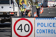 Police man a road block on the Forrest Highway south of Perth set up to control the spread of Covid-19 across the state.