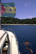 The skipper of a yacht swims in front of Macaco (Monkey) beach. The flag on the top left is Sao Tome and Principe national flag.
