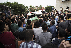 May 6, 2018 - Gaza City, The Gaza Strip, Palestine - Members of the Islamist movement Hamas' military wing Al-Qassam Brigades gather around the bodies of six of their comrades who were killed in an unexplained explosion the night before, during their funeral in Deir al-Balah in the central Gaza strip on May 6, 2018. Gaza's health ministry confirmed six people were killed and three others wounded in what residents said appeared to be an accidental explosion in the Az-Zawayda area of the central Gaza Strip. Al-Qassam Brigades blamed Israel for the explosion without providing details or proof, saying incident occurred during a ''complex security and intelligence operation'' and calling it a ''serious and large security incident' (Credit Image: © Mahmoud Issa/Quds Net News via ZUMA Wire)