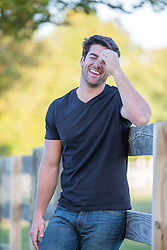 handsome All American man leaning against a rustic fence laughing