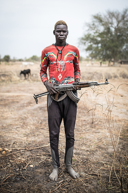 Cows are the most valuable and stable asset families can own and they are often at the centre of clashes between communities. Mangor is 23 years old. Like many other young men from his community, he carries a weapon to defend his cattle. South Sudan, 2020.