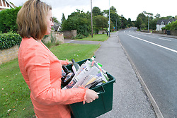 Woman carrying curb side recycling collection box out onto the pavement ready for collection,