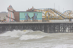 Licensed to London News Pictures. 21/05/2021. Brighton, UK. High winds hit Brighton Pier as the Met Office issue weather warnings for high wind speeds and prolonged rain today. Rain and storm winds are expected today with wind speeds in excess of 55mph along the South Coast and London as the miserable May Spring weather continues. However, sun is on the way for the May Bank Holiday with temperatures expected to hit 22c by the end of the month. Photo credit: Alex Lentati/LNP