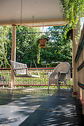 Porch swings offer the perfect ambiance to allow casual conversation with passing neighbors and enough room to curl up with a good book on a sunny afternoon.  PHOTO BY: JEFF JANOWSKI PHOTOGRAPHY