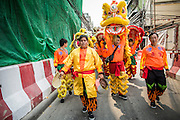 """09 FEBRUARY 2013 - BANGKOK, THAILAND:  Chinese Lion Dancers walk down a sidestreet in Chinatown in Bangkok. Bangkok has a large Chinese emigrant population, most of whom settled in Thailand in the 18th and 19th centuries. Chinese, or Lunar, New Year is celebrated with fireworks and parades in Chinese communities throughout Thailand. The coming year will be the """"Year of the Snake"""" in the Chinese zodiac.   PHOTO BY JACK KURTZ"""