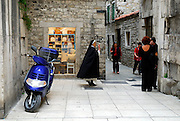 Christian nun walking through narrow streets, Diocletian Palace, Split, Croatia