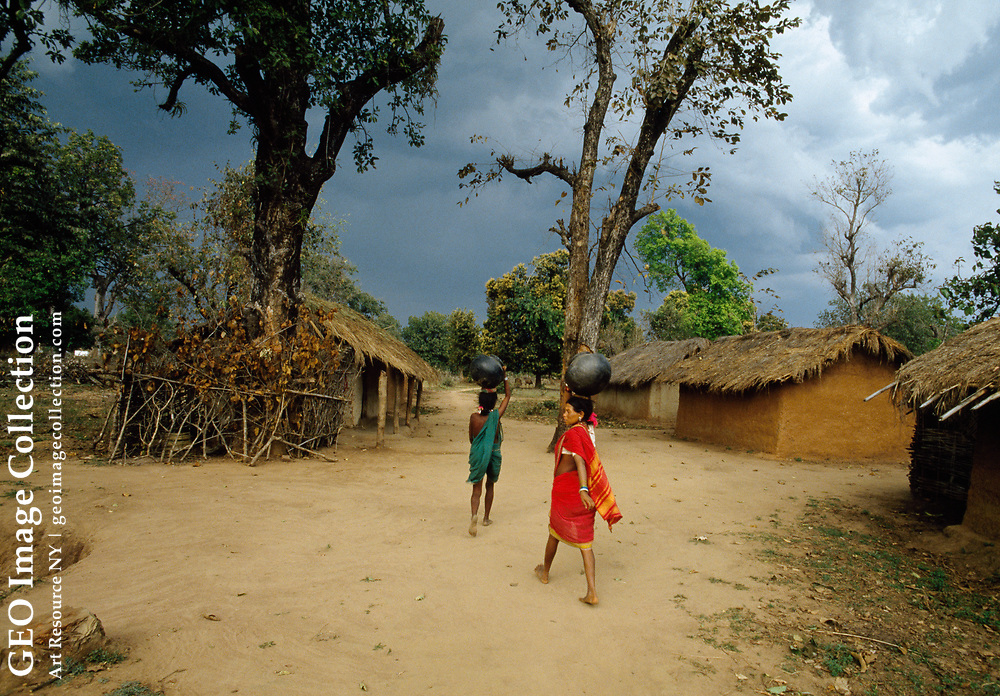Women carry water at this resettlement village. This village is made up of trib als who represent the lowest of the Indian caste system.  The village was moved out of Kanha National Park to this government-built village when the park was created. Most of the children in this village are malnourished.
