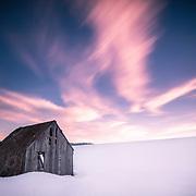 Winter Barn Sunset. A long exposure blurs the clouds. Idaho