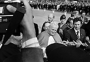Pope John Paul II greets the crowds who turned up at Dublin airport to welcome him at the start of his three-day visit to Ireland. Behind him (partly obscured) is Papal Nuncio Archbishop Gaetano Alibrandi, and behind the archbishop is Taoiseach Jack Lynch. <br />