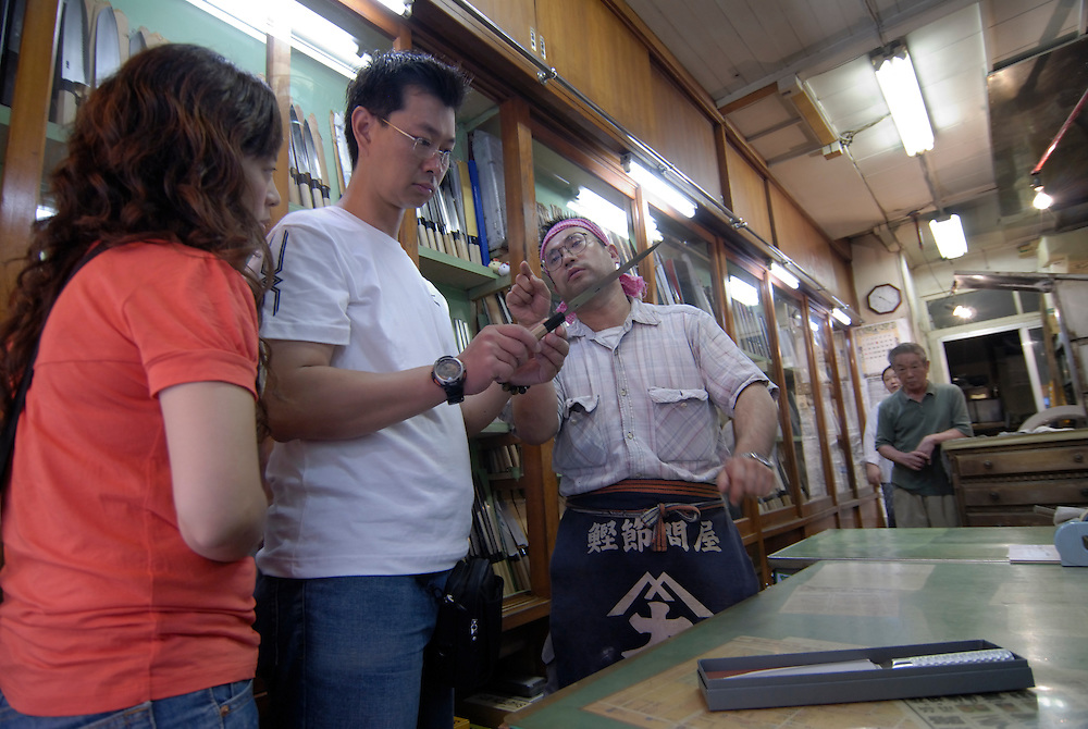 Talking to customers in the knife shop.