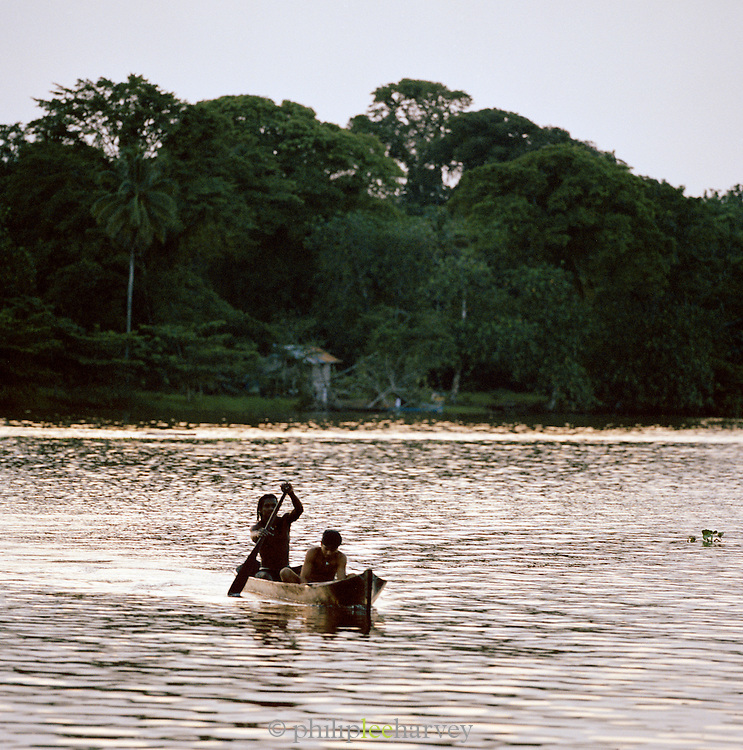Locals paddle a canoe through rainforest at the Tortuguero National Park, East Coast, Tortuguera, Limon, Costa Rica