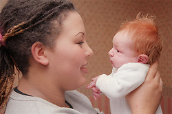 Mother holding newborn baby daughter smiling,
