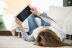 Woman lying on back with digital tablet