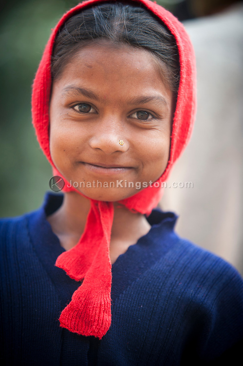 Portrait of a young Indian girl wearing a red scarf, Pushkar, India.