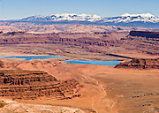 Intrepid Potash Inc. mines potash with a water dissolution and evaporation process at Cane Creek Facility, near Moab, Utah, USA. (Photo taken from a viewpoint on Island in the Sky in Canyonlands National Park, Utah, USA.) Water from the nearby Colorado River is pumped through injection wells into the underground mine. The water dissolves the potash from layers buried 3,000 feet underground. The mineral-laden water (brine) is piped to 400 acres of shallow ponds where the water evaporates, aided by 300 days of sunshine and very low humidity, leaving potash (potassium chloride) and salt (sodium chloride) crystals. A blue dye, similar to food coloring, is added to assist evaporation (saving the burning 400,000 tons of coal each year). The solar ponds are lined with heavy vinyl to prevent brine from leaking into the ground and the Colorado River. Holding ponds catch any spills and return potassium-rich brine to the ponds. The snow-dusted La Sal Mountains reach 12,780 feet in elevation.