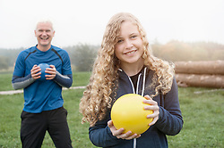 Teenage Girl with her father exercising with yoga ball on the field and smiling during dawn, Bavaria, Germany
