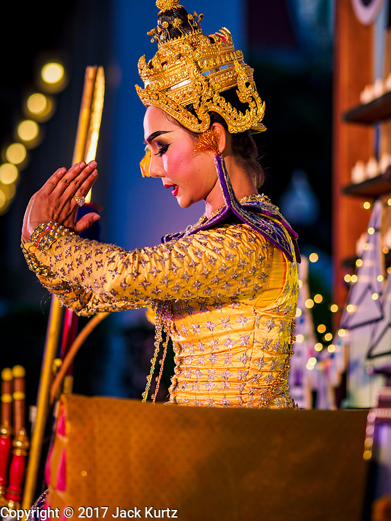 """03 NOVEMBER 2017 - BANGKOK, THAILAND: A traditional Thai dancer performs during Loi Krathong at Wat Prayurawongsawat on the Thonburi side of the Chao Phraya River. Loi Krathong is translated as """"to float (Loi) a basket (Krathong)"""", and comes from the tradition of making krathong or buoyant, decorated baskets, which are then floated on a river to make merit. On the night of the full moon of the 12th lunar month (usually November), Thais launch their krathong on a river, canal or a pond, making a wish as they do so. Loi Krathong is also celebrated in other Theravada Buddhist countries like Myanmar, where it is called the Tazaungdaing Festival, and Cambodia, where it is called Bon Om Tuk.     PHOTO BY JACK KURTZ"""